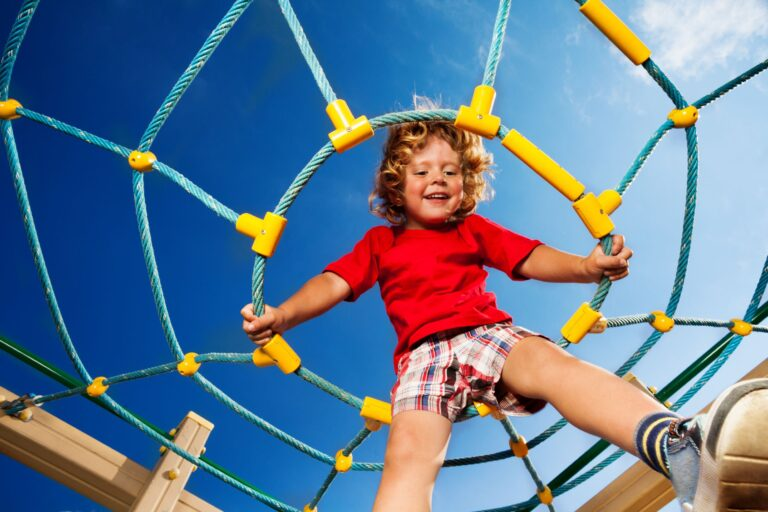 Happy little three years old child boy sitting on the web on playground and smiling ready to jump