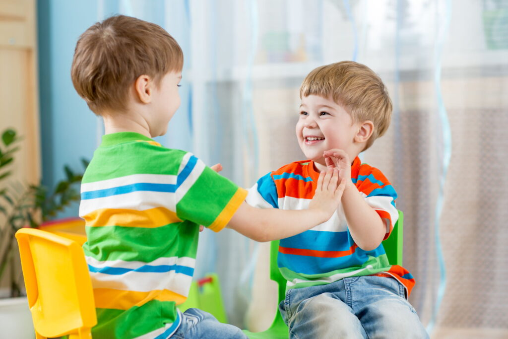 Little boys play clapping game together in speech therapy.