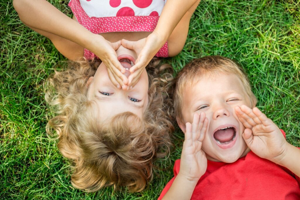 Funny kids shouting outdoors. Happy children lying on green grass. Communication concept