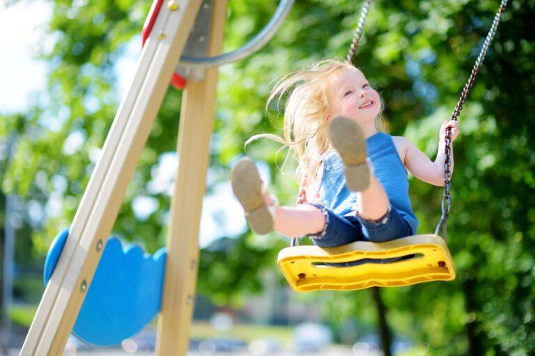 Little girl swinging on playground.