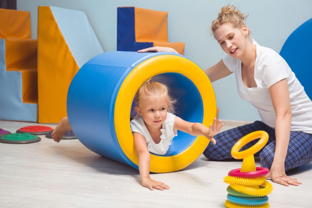 Little girl positioned prone in barrel reaching to stack rings in occupational therapy.