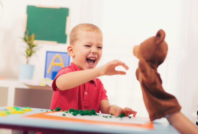 Little boy communicating with puppet in pediatric speech therapy.