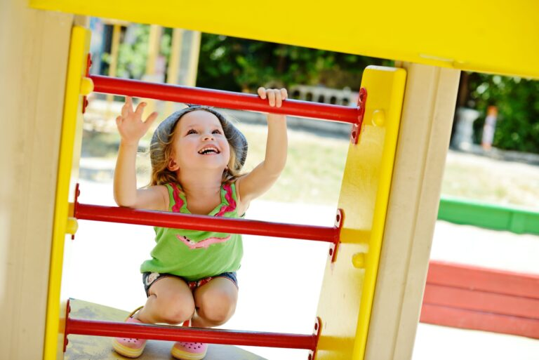 Little girl ready to climb ladder on playground.